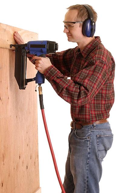 worker using an air-powered nail gun